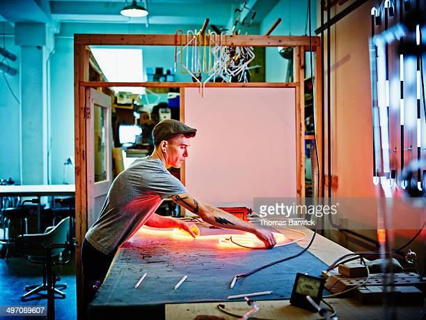 Neon artist working on piece in loft