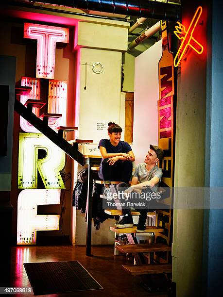 Neon artists on stairs surrounded by neon signs