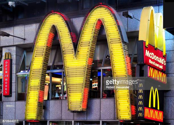 A neon 'golden arches' sign identifies a McDonald's fast food restaurant in Midtown Mahnattan New York City