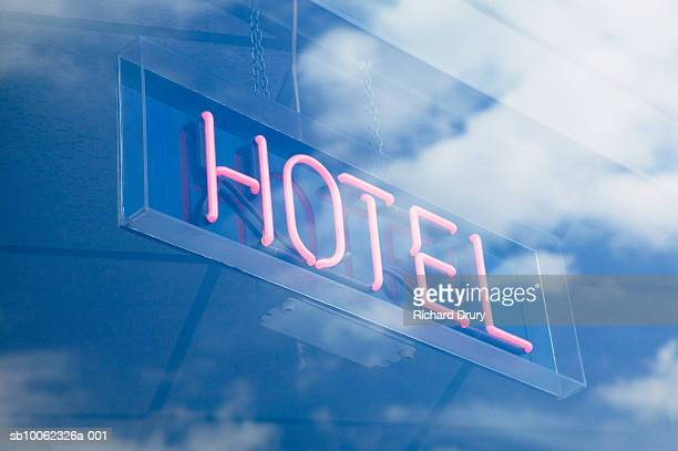 neon hotel sign in window reflecting sky with clouds, low angle view - richard drury stock pictures, royalty-free photos & images