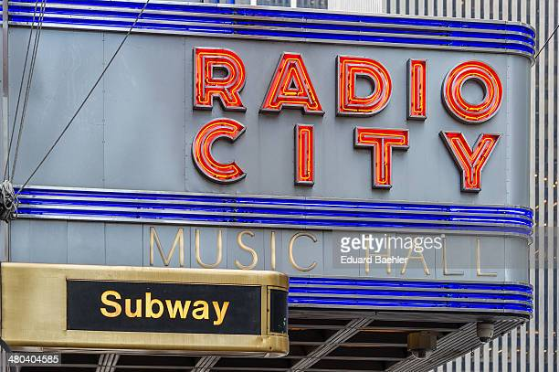 Neon lettering of Radio City Music Hall with subway lettering below