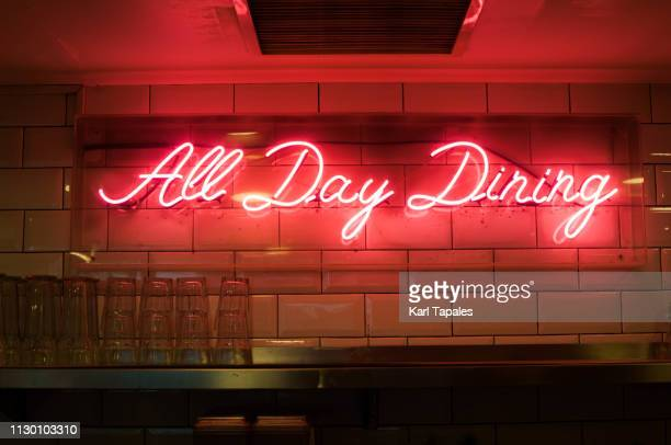 "neon light with a short phrase ""all day dining"" - pink tube photos et images de collection"