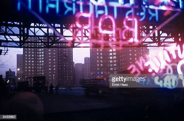 Neon lights in a bar window seen against the background of tower blocks with their windows bright in the evening light