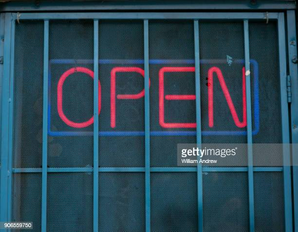 """neon """"open"""" sign behind security bars - irony stock pictures, royalty-free photos & images"""