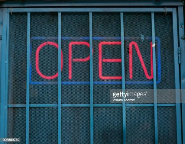 """neon """"open"""" sign behind security bars - irony stockfoto's en -beelden"""