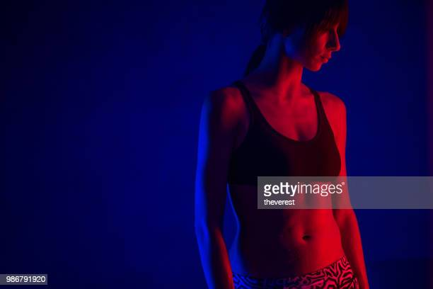 neon portrait of a woman stretching in the studio - neon coloured stock pictures, royalty-free photos & images