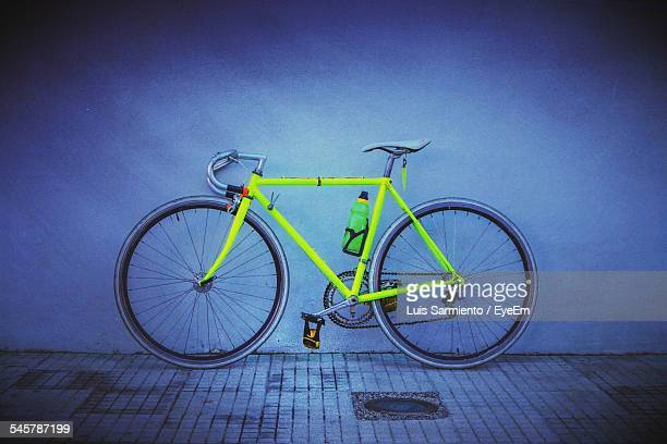 Neon Racing Bicycle Against Wall On Sidewalk