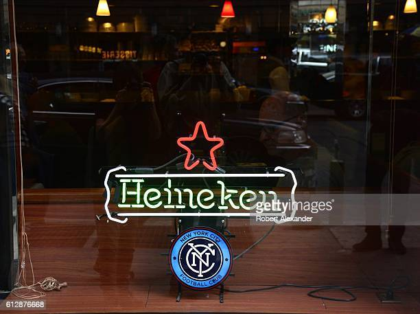 A neon sign advertises Heineken beer in the window of a bar in New York City The sign also promotes the New York City Football Club an American...
