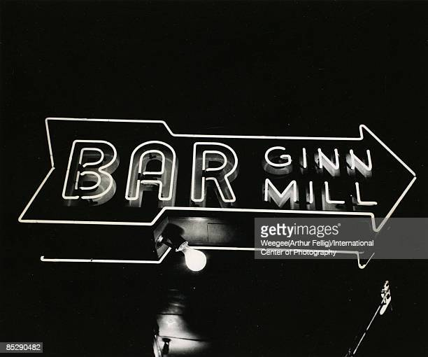 A neon sign in the shape of an arrow points the way to the 'Bar Ginn Mill' ca1945 New York A bare light bulb hangs under the sign Photo by...