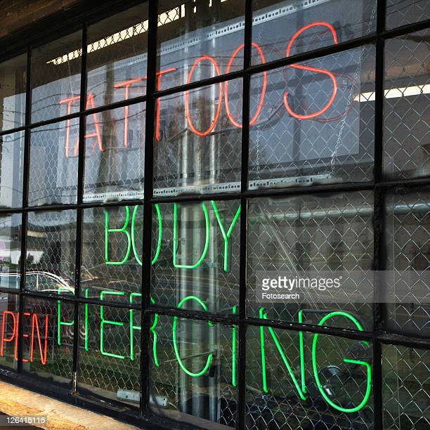 neon sign in window for tattoos and body piercing. - body piercings stock photos and pictures