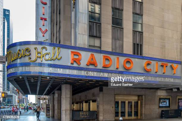 Neon sign of Radio City Music Hall in Manhatten with view along 6th avenue