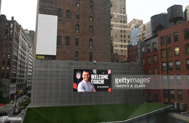 TOPSHOT A neon sign on the side of a building shows the new US Soccer Womens National Team head coach Vlatko Andonovski before a press conference...