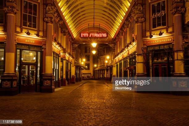 Neon sign reading 'I'm staying' hangs illuminated at Leadenhall Market in the City of London, U.K., on Monday, April 15, 2019. Job vacancies in...