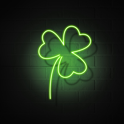 Neon signboard in the shape of a clover trefoil on a brick wall background. The symbol of the holiday St. Patrick's Day. 1197182624