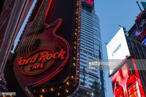 Neon signs and advertisements including the Hard Rock Cafe are illuminated on Broadway near Times Square New York