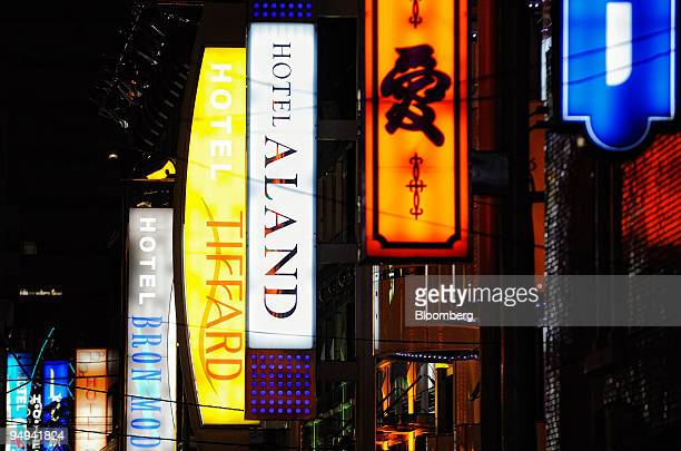 Neon signs hang from the exterior of love hotels in the Kabukicho district of central Tokyo Japan on Sunday April 19 2009 While Japanese companies...