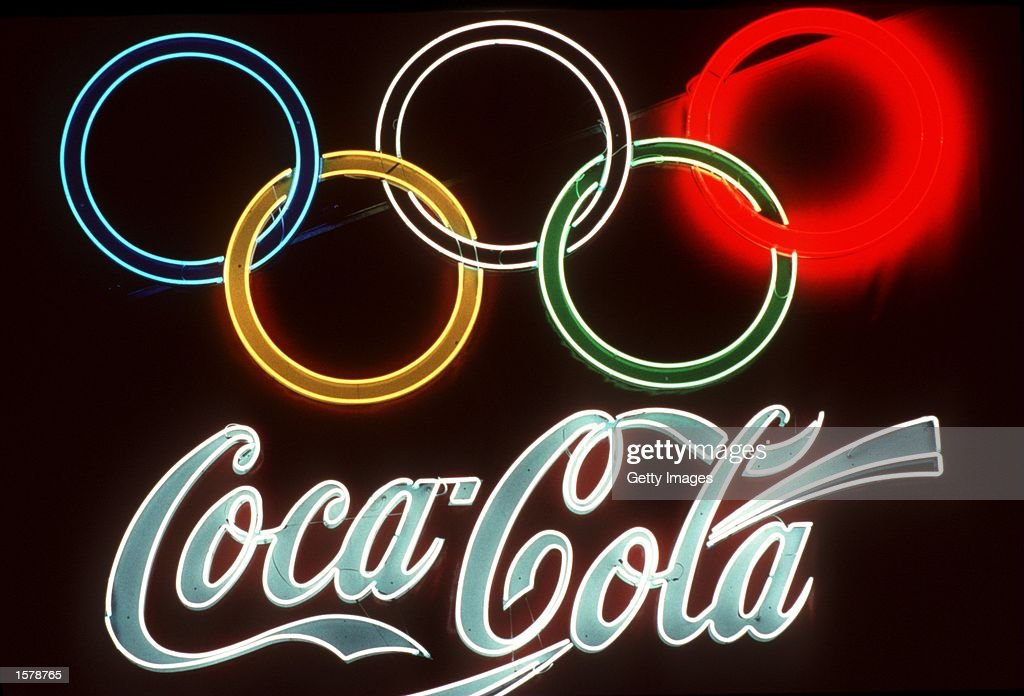 1992:  A neon signs of Olympic sponsor Coca Cola glows bright on a dark wall during the 1992 Olympic : News Photo