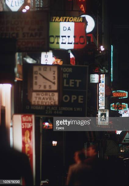 Neon signs on a Soho street including advertising for an Italian restaurant and adult revues October 1970