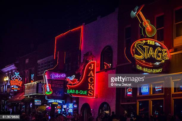 neon signs on lower broadway (nashville) at night - nashville stock pictures, royalty-free photos & images