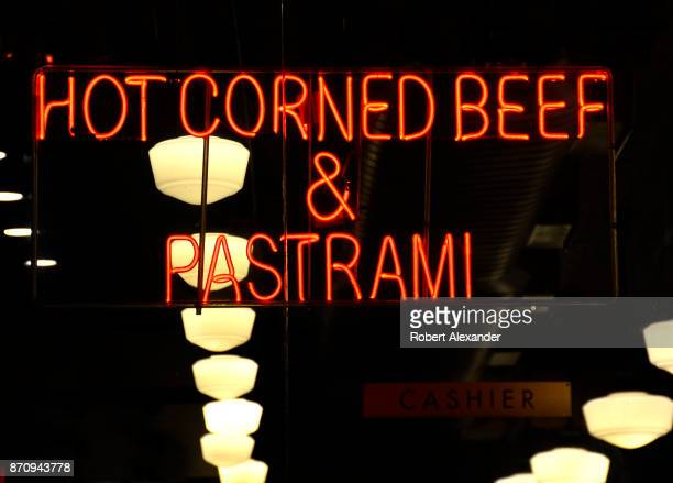 Neon window signs advertise a Midtown Mahnattan delicatessen shop's hot corned beef and Pastrami sandwiches