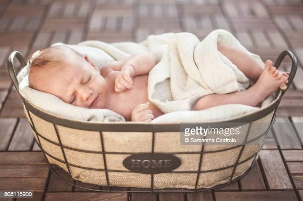 Neonato maschio dorme nella cesta.