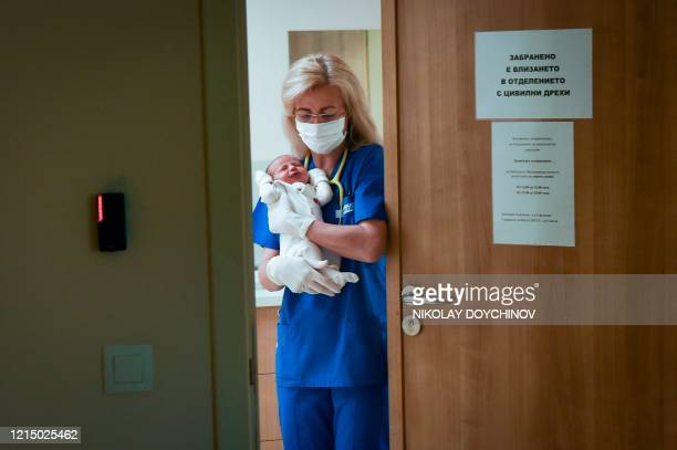 Neonatologist Valentina Gerginova holds a newborn prior to administering a dose of BCG vaccine in Vita private hospital in Sofia on May 20 20120 As...