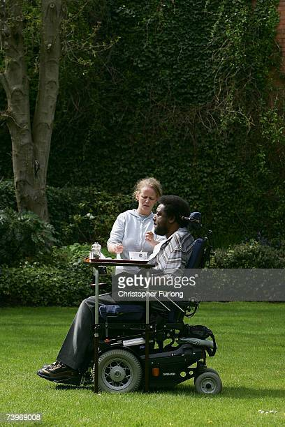 NeoNazi attack victim Noel Martin eats his lunch in the garden of his home with the help of one of his personal assistants on April 25 in Birmingham...
