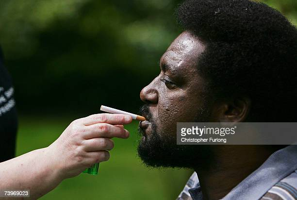 NeoNazi attack victim Noel Martin smokes a cigarette in the garden of his home with the help of one of his personal assistants on April 25 in...