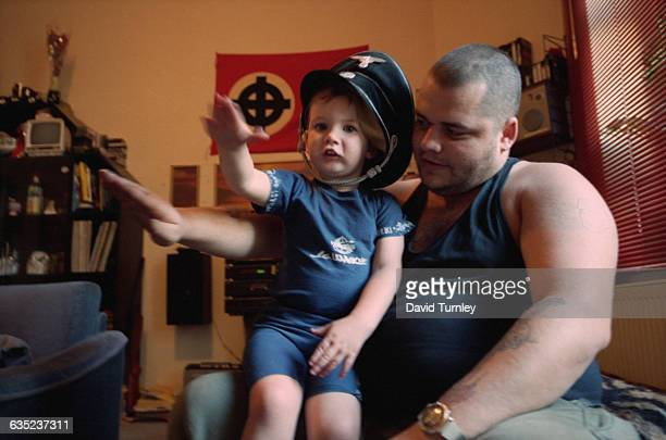 NeoNazi leader Roy Brandt known as Bomber looks encouragingly at his threeyear old son as the two of them give the Nazi salute The boy wears a Third...