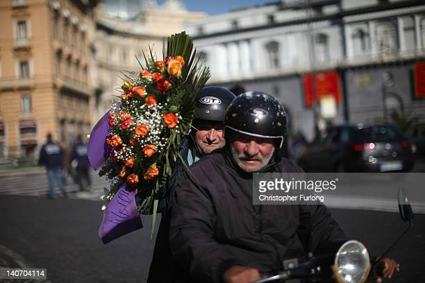 Neopolitans ride their scooter on November 17 2011 in Naples Italy Naples is famed for it's narrow streets pizza Mount Vesuvius and Unesco protected...