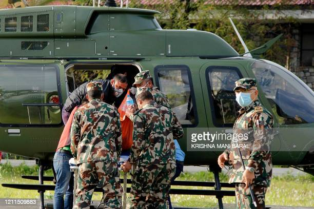Nepal army and volunteers carry the bodies of South Korean trekkers and a Nepali guide who were among seven people missing after a Himalayan...