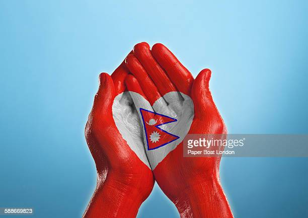 nepal heart shaped flag painted on a hand - nepali flag stock pictures, royalty-free photos & images