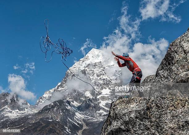Nepal, Himalaya, Solo Khumbu, Ama Dablam, man standing on rock throwing rope