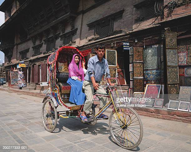 Nepal, Kathmandu, Durbar Square, young woman riding in rickshaw