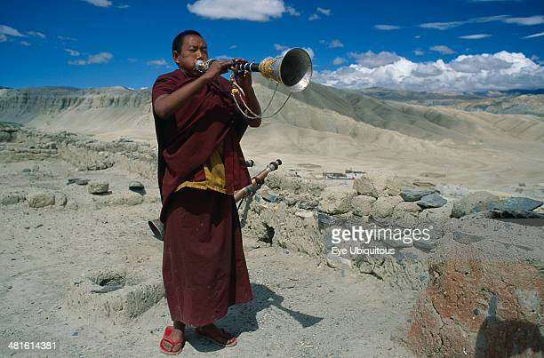 Nepal Mustang Namgyal Gompa Tibetan Buddhist monk blowing long decorated horn on monastery roof to summon the faithful to prayer Barren mountainous...