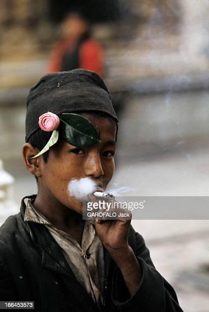 Nepal Népal mars 1970 Un jeune garçon coiffé du bonnet gris décoré d'une fleur de camélia rose fume une cigarette