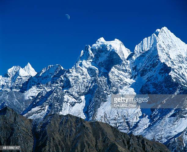Nepal Sagarmatha National Park Himalayan mountain peaks with moon above just visible in deep blue sky
