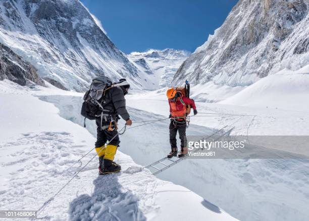 nepal, solo khumbu, everest, sagamartha national park, mountaineers crossing icefall at western cwm - mt. everest stock pictures, royalty-free photos & images