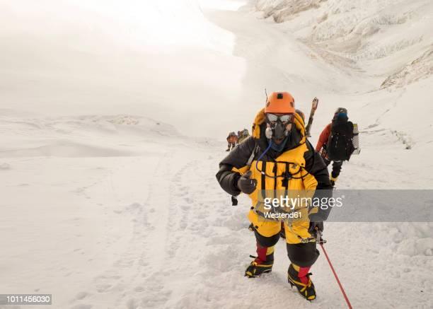 nepal, solo khumbu, everest, sagamartha national park, roped team ascending, wearing oxigen masks - himalaya photos et images de collection