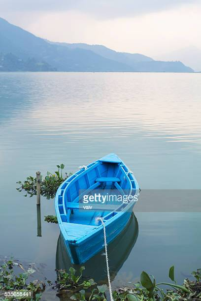 Nepal, Western Region, Gandaki Zone, Pokhara, Mansawar, Phewa Lake, Blue rowboat anchored in lake with silhouette of mountain in background