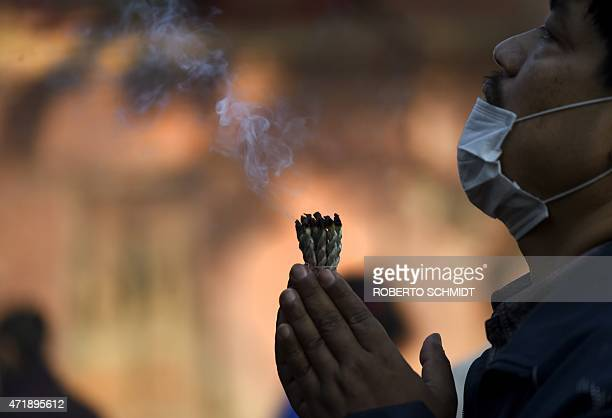 A Nepales man holds lit wicks as he offers a prayer in front of a statue of Hindu diety Kaal Bhairab in the Durbar Square neighbourhood of Kathmandu...
