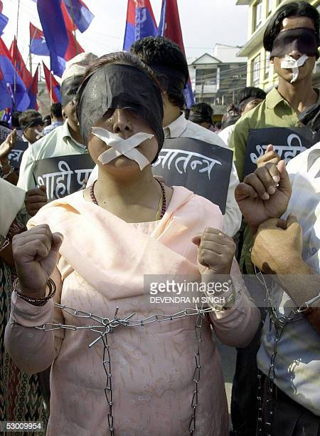 Nepalese activists of the opposition Democratic National Youth Association have black bands covering their eyes white gags on their mouths and their...