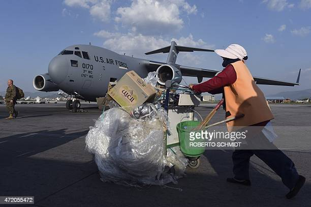 A Nepalese airport cleaner pushes a trolley full of trash in the tarmac near a US military C17 transport plane that arrived at Kathmandu's...