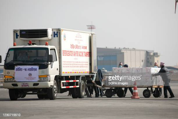 Nepalese airport ground staff unload boxes carrying AstraZeneca/Oxford University vaccine, manufactured under license by Serum Institute of India...