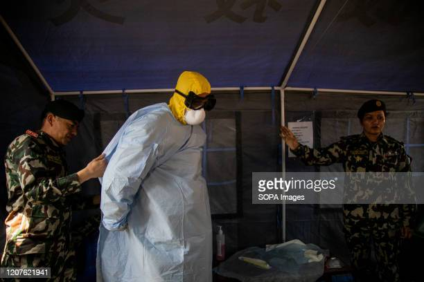 Nepalese Army officer demonstrates how to wear a protective suit inside a quarantine model zone at the Nepalese Army headquarters amid concerns about...