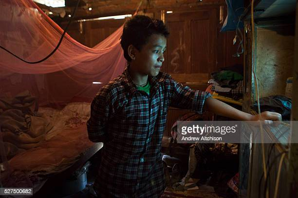 A Nepalese boys watches a television in his bedroom in Kathmandu Nepal His home is made from bricks and wood with a corrugated iron roof He used to...