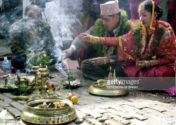 Nepalese bride and a groom are helped by a priest to perform their wedding rituals according to Nepalese Hindu traditions on the occasion of Basant...