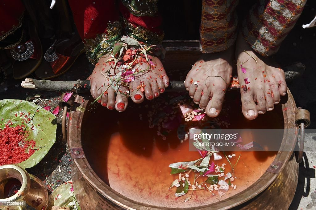 A Nepalese bride and groom place their feet above a vat during a wedding ceremony at a Hindu temple on May 3, 2015. International aid continues to pour into Nepal to help victims of a massive earthquake on April 25 killed at least 7,200 people and devastated vast swathes of one of Asia's poorest countries.
