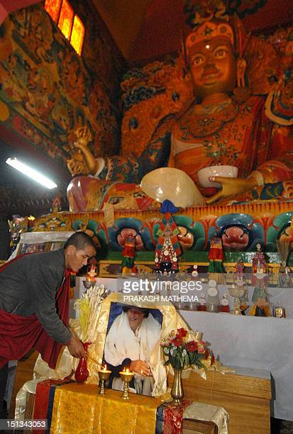 A Nepalese Buddhist monk lights an oil lamp in front of a portrait of Sir Edmund Hillary as he performs Buddhist rituals for the deceased New Zealand...
