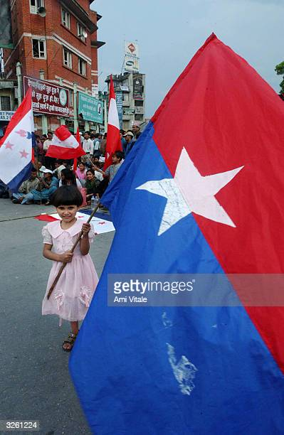 Nepalese child holds a flag during a rally by activists protesting against King Gyanendra that brought the Himalayan kingdom to a halt for the third...